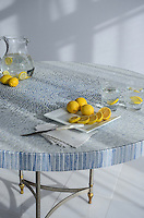 Mist, a hand chopped stone mosaic shown in tumbled Ming Green, Kays Green, Celeste, Calacatta, Blue Macauba and Lettuce Ming with Blue Macauba trim, is shown here on a custom table.