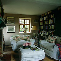 Loose covers in fresh white linen and floral scatter cushions look pretty against grey walls in the living room of Arne Maynard's house in Lincolnshire