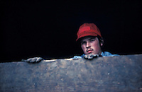 One man in red hat inside railroad freight car that has just delivered fresh potatos to potatoe chip snack factory
