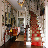 The entrance hall is decorated with a striking wallpaper offset by a highly polished wooden floor and a red stair carpet
