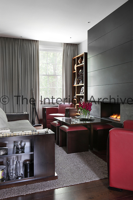 One half of the sitting room faces an open-fire for complete relaxation, while heavy drapes and subtle spotlighting gives the apartment a subdude lighting