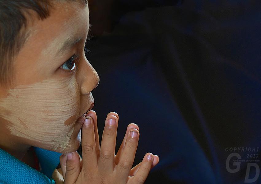 Young Boy praying at the Maha Muni during Full Moon Festival, Mandalay,  Myanmar, Burma,