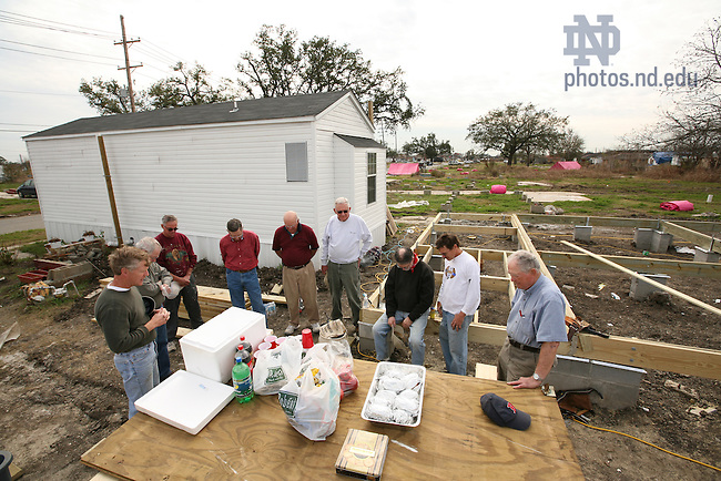 Steven Meriwether, left, pastor of the St. Charles Avenue Baptist Church, leads a group of construction volunteers in prayer before they break for lunch.  They are rebuilding this Lower Ninth Ward home for the woman who lives in the temporary housing behind them.