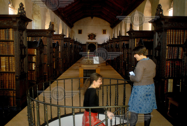 A library assistant and a student in the Old Library of St John's College, University of Cambridge.