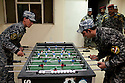 "Iraqi policemen play Foosball at the headquarters of the 5 Division 2nd Brigade Iraqi Federal Police August 25, 2010 in Baghdad, Iraq. Much of the headquarters contains items such as the foosball table, AC's, and sandbag security walls, which were left behind by American units who once commanded the base and have now been ""inherited"" by the Iraqi security forces.   ."