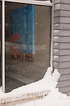 Blowing snow drifting against the art gallery's window and reflected in the glass belies the summer image of Rehoboth Beach on display inside.  Rehoboth Beach, Delaware, USA, during the blizzard of February 2010.