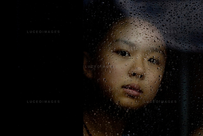 A girl peers out of a city bus window on a rainy day in Beijing, China on Thursday, August 14, 2008.  Kevin German