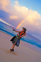A smiling Hawaiian girl performs hula with a rainbow over the Island of Kahoolawe in the background at Big Beach, Makena, Maui.