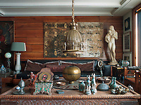 """Above the sofa, custom-made by Hakan Ezer, hangs a painting by contemporary artist Canon Tolon. The statue is """"Two Sisters"""" by Kai Nielsen. The coffee table is from Afganistan and the chandelier is early twentieth century from Belgium"""