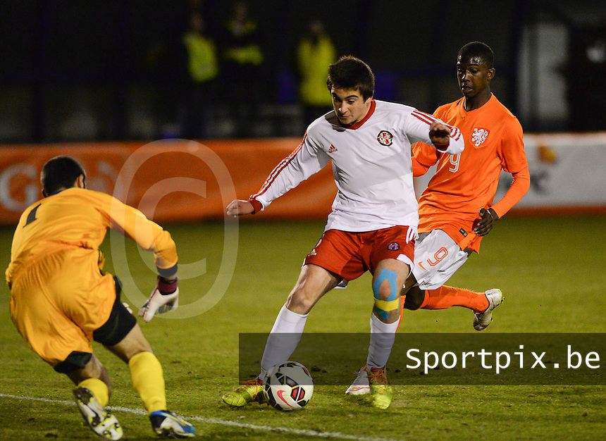 20150312 - SCHIJNDEL , NETHERLANDS  : Georgian Akaki Kurashvili (middle) pictured defending the ball from Dutch Nigel Robertha (right) during the soccer match between Under 17 teams of The Netherlands and Georgia  , on the first matchday in group 3 of the UEFA Elite Round Under 17 at Sportpark Zuideinderpark , Schijndel , The Netherlands . Thursday  12 th March 2015 . PHOTO DAVID CATRY