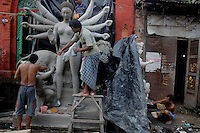 INDIA (West Bengal - Calcutta)  2008, Artisans working at Kumortuli. Kumortuli in North Calcutta is the hub of Durga idol makers. During the other time of the year the artists engage themselves in prepairing other idols and masks depending on the assignments. But the most of the earning they aquire from making Durga idols. A Durga idol can cost up to 7000 usd. Which is a big price in Indian Currency.  Durga Puja Festival is the biggest festival among bengalies.  As Calcutta is the capital of West Bengal and cultural hub of  the bengali community Durga puja is held with the maximum pomp and vigour. Ritualistic worship, food, drink, new clothes, visiting friends and relatives places and merryment is a part of it. In this festival the hindus worship a ten handed godess riding on a lion armed wth all possible deadly ancient weapons along with her 4 children (Ganesha - God for sucess, Saraswati - Goddess for arts and education, Laxmi - Goddess of wealth and prosperity, Kartikeya - The god of manly hood and beauty). Durga is symbolised as the women power in Indian Mythology.  In Calcutta people from all the religions enjoy these four days of festival in the moth of October. Now the religious festival has become the biggest cultural extravagenza of Calcutta the cultural capital of India. Artistry and craftsmanship can be seen in different sizes and shapes in form of the idol, the interior decor and as well as the pandals erected on the streets, roads and  parks.- Arindam Mukherjee