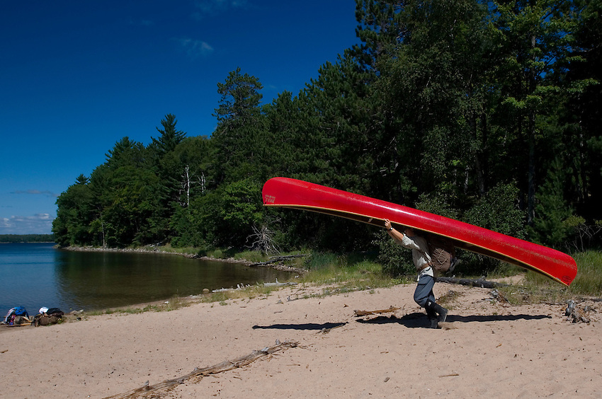A canoeist portages a red canoe between Clark and Crooked Lakes at Sylvania Wilderness Area of Ottawa National Forest near Watersmeet Michigan.