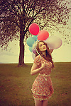 A young girl with pale skin and blond hair wearing a floral dress standing with colorful balloons outdoors in spring