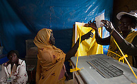 An election official explains the ballot paper to a woman at a polling station in Malakal, South Sudan. On 9th January 2011 Southern Sudan's people voted in a referendum on whether to become independent from the North.
