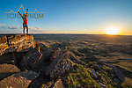 woman hiker with hands in the air watching sun go down standing on a boulders prairie eastern montana