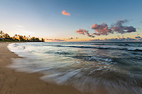 Sunset colors reflect over the waters of a beach in Waialua, North Shore, O'ahu.