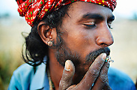 A rajasthani man smoking the last bits of his bidi (the Indian cigarette), Pushkar Camel Fair, Rajasthan.