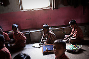 10 year old Sunil Rajaram (centre) attends his classes in a government run school in Caregaon, Thane, Maharashtra. Students from lower income group families attend the class during the day and later at night sleep in the same classroom. These schools run a specially designed concept of 'aflatoon' as part of the curriculam whereby students are made aware of their child as described in the convention of rights of child. These students are made aware of right to survival, right to protection, right to development and right to participation.