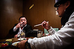 Soma, Fukushima prefecture, November 8 2013 - Kazuaki S., boss of a local yakuza gang, dinning at a restaurant with Minoru S., a younger member, before heading to a strip club owned by Kazuaki S. The decontamination works at Fukushima Daiichi Nuclear power plant and around has increased the number of customers for his club and for the various activities of the japanese mafia.