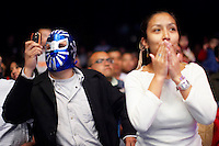 Spectators, one of whom is wearing a Luchador's (fighter's) mask, watch the match. Lucha Libre is a style of wrestling started in Mexico in 1933. The name means Free Fight, and matches tend to be focussed on spectacle and theatre with fans cheering for their favourite characters, who wear masks while jumping from the ropes, flipping opponents, and occasionally crashing into the crowd..&copy;Jacob Silberberg/Panos/Felix Features.