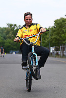 Jun 11, 2016; Englishtown, NJ, USA; NHRA funny car driver Del Worsham rides a wheelie on his bicycle during qualifying for the Summernationals at Old Bridge Township Raceway Park. Mandatory Credit: Mark J. Rebilas-USA TODAY Sports