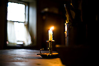 Candle in the wind:a single  open window provides a light breeze to gently blow the flame on a candle in a darkened room.