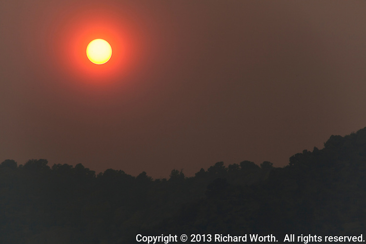Along US Highway 50 between Canon City and Salida, Colorado, the afternoon sun glows red through wildfire smoke.
