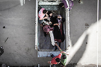 Women Civilians lay down at the back of a truck as they are removed from a hospital in Tarik Al Bab neighborhood, after they were injured by aircraft strike on a highway outskirsts of Aleppo City.