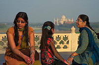 Local Indian Visitors enjoy the view from the Agra Fort with the Taj Mahal in the background, India