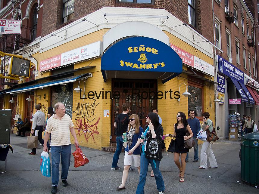 Pedestrians walk past a closed Senor Swanky's Mexican Restauarant on Bleecker Street in the New York neighborhood of Greenwich Village on Saturday, April 18, 2009. (© Richard B. Levine)