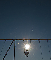 Boy on swing with rays of sunburst star pattern against blue sky