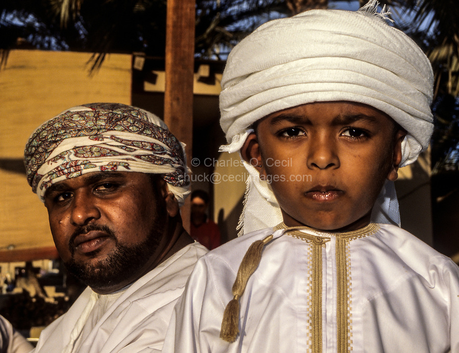 Muscat, Oman.  Young Omani Boy and his Father.  A yellow tassel several inches long, called a kashkusha or a frakha, hangs from the neckline of his dishdasha.  The kashkusha is often perfumed. Muscat Festival.