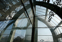 Tropical Rainforest Glasshouse (formerly Le Jardin d'Hiver or Winter Gardens), 1936, René Berger, Jardin des Plantes, Museum National d'Histoire Naturelle, Paris, France. Low angle view of the main Art Deco style entrance fringed by leaves, seen against the morning light.