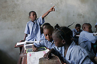 May, 2005, Cotonou, Benin --- Boy Raising Hand in Classroom of Private Elementary School --- Image by &copy; Owen Franken/Corbis