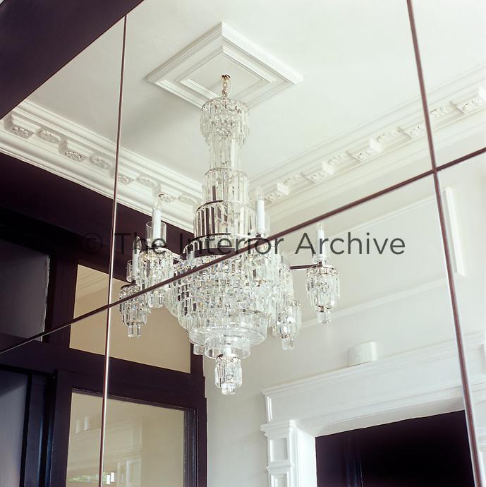 An elaborate chandelier is reflected in a mirrored wall, giving a sense of space to the room.