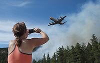 A bystander videos fire suppression tankers in action during a forest fire in Peachland, British Columbia.