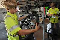 NWA Democrat-Gazette/FLIP PUTTHOFF<br /> Blake Harrison (left) demonstrates how to put the tire back on the wheel after replacing the tube by starting at the valve stem and working around the wheel. His twin brother, Harrison Phillips, works on a tire at right.