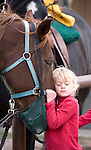 USA. Wyoming. Grand Tetons National Park. Young girl gives affection to a horse in a Tetons stable. MR