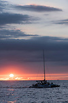 Kona, Big Island of Hawaii, Hawaii; sunset over the Pacific Ocean silhouettes a catamaran sail boat