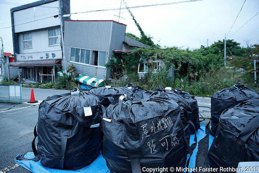 Earthquake damage and decontamination waste storage in Tomioka, Japan. Laborers are working to decontaminate Tomioka, in the Fukushima Exclusion Zone, four and a half years after the Fukushima Daiichi nuclear power plant disaster. Full caption to come.<br /> <br /> &copy; Michael Forster Rothbart Photography<br /> www.mfrphoto.com &bull; 607-267-4893<br /> 34 Spruce St, Oneonta, NY 13820<br /> 86 Three Mile Pond Rd, Vassalboro, ME 04989<br /> info@mfrphoto.com<br /> Photo by: Michael Forster Rothbart<br /> Date:  9/26/2015<br /> File#:  Canon &mdash; Canon EOS 5D Mark III digital camera frame A26529