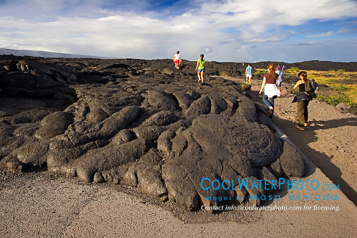 Park visitors and hikers walking over Pahoehoe lava from 1992 to 2003 eruption which devastated Chain of Craters Road, Hawaii Volcanoes National Park, Kilauea, Big Island, Hawaii..