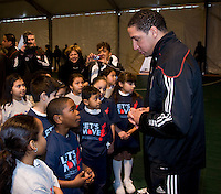 DC United's Judah Cooks talks to a group of local students during a US Soccer Foundation clinic held at City Center in Washington, DC.