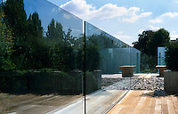 A wood bench stands next to the glass wall which acts as a safety barrier and produces a reflective mirror effect