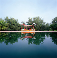 An imaginative and exotic daybed overlooks the still waters of this outdoor swimming pool