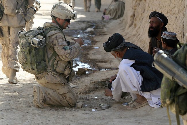A soldier with November Company, 3rd Battalion, Royal Canadian Regiment  accepts a glass of steaming hot tea offered to him by an elderly man during an operation in the village of Nakhonay, southwest of Kandahar, Afghanistan.  Oct. 7, 2008. DREW BROWN/STARS AND STRIPES