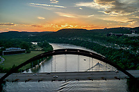 This is an aerial image of the Austin 360 bridge or Pennybacker bridge at sunset taken from above the bridge with Lake Austin and the nice colors in the sky with the texas hill country scenery. You can see a few boats still on the water enjoying the nice weather.