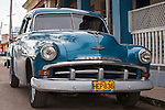 Cojimar, Cuba; a blue classic 1954 Plymouth parked on the street in Cojimar, the setting for Ernest Hemingway's The Old  Man and the Sea
