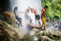 Haitians pilgrims, both followers of Catholicism and Voodoo, perform a bathing ritual under the waterfall during the annual religious pilgrimage in Saut d'Eau, Haiti, July 16, 2008. Every year in summer thousands of pilgrims from all over Haiti make the religious journey to the Saut d'Eau waterfall (100km north of Port-au-Prince). It is believed that 150 years ago the spirit of Virgin Mary (Our Lady of Mount Carmel) has appeared on a palm tree close to the waterfall. This place became a main pilgrimage site in Haiti since then. Haitians wearing only underwear perform a bathing and cleaning ritual under the 100-foot-high waterfall. Voodoo followers (many Haitians practise both voodoo and catholicism) hope that Erzulie Dantor, the Voodoo spirit of water, manifest itself and they get possessed for a short moment, touched by her presence.