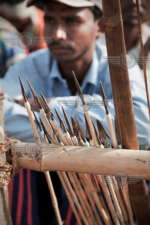 A man sits behind a rack of arrows and listens to speeches at a protest rally by Santal Adavesi tribespeople, on the West Bengal / Jharkhand border. They are demonstrating against the destruction of their land as a consequence of the excavation of a stone quarry.