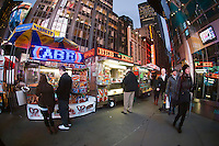 Diners purchase street food from street food vendors outside of NASDAQ in Times Square in New York on Wednesday, November 23, 2011. (© Frances M. Roberts)